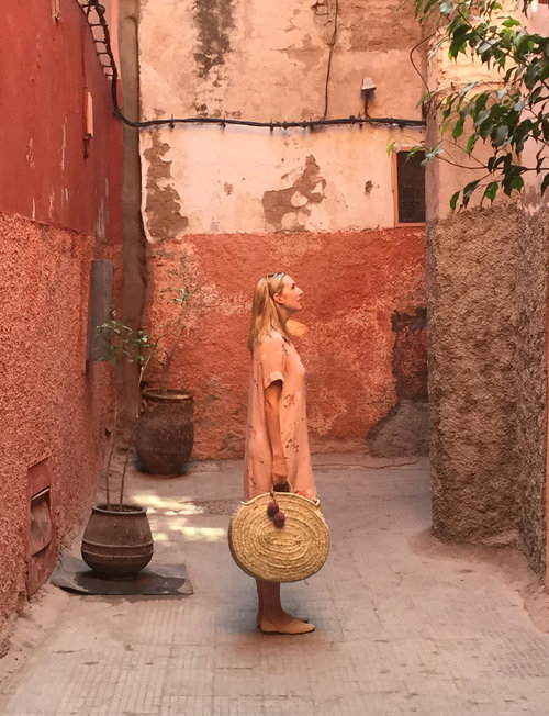 Milicent, owner and designer for Artemis Design Co., wearing raffia shoes and carrying a straw bag.