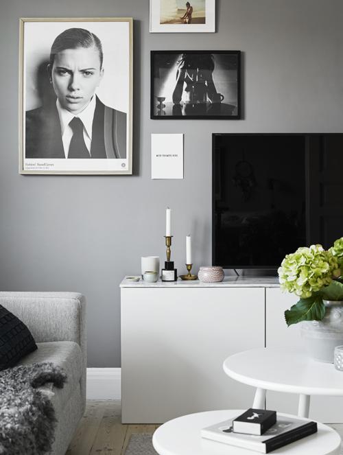 Tv-bänken består av tre köksskåp och en bänkskiva från Ikea. Ljusstakarna på bänken är loppisfynd och doftljusen kommer från Voluspa och Balmuir. Soffa, Bolia, satsbord, Ellos. Fotokonst, Fotografiska. På borden syns ett tändsticksaskfodral från Nordiska galleriet och en porslinskruka från House doctor. Hortensia är en av Jasminas favoritväxter. Väggen är målad i Alcros färg Lunar grey.
