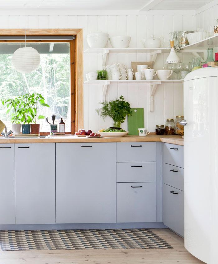 Köket har härligt ljusinsläpp från glasdörren, som leder ut till den stora terrassen. Inredning från Ikea. Vitt porslin från Keith Brymer Jones. Kylskåp från Smeg. Plastmatta, Pappelina. Taklampa, Ikea.