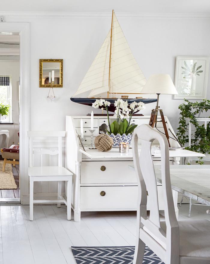 Golvlampan och ljushållaren på väggen är av egen design. Vita stolen är arvegods. Sekretären är köpt avlutad i en antikbod och har målats vit. Stor modellbåt från Hulténs i Staffanstorp. Ljusstakar, Degeberga antik- och samlarmarknad. Repknut, Zara home. Blomkrukan är en gåva. Ljuslykta, Ikea. Bordslampa, Esperöds herrgård.