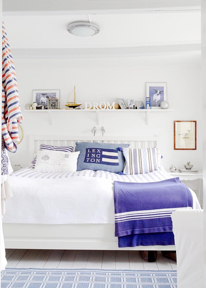 Säng, vägglampor och fåtölj från Ikea. Sängkläder, Lexington och pläd, Himla. Mattan är en gåva.