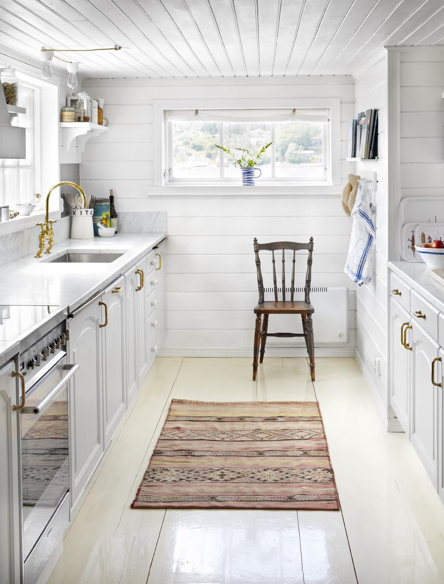 Köket är i vitt med inslag av blå, röda och guldiga detaljer.
