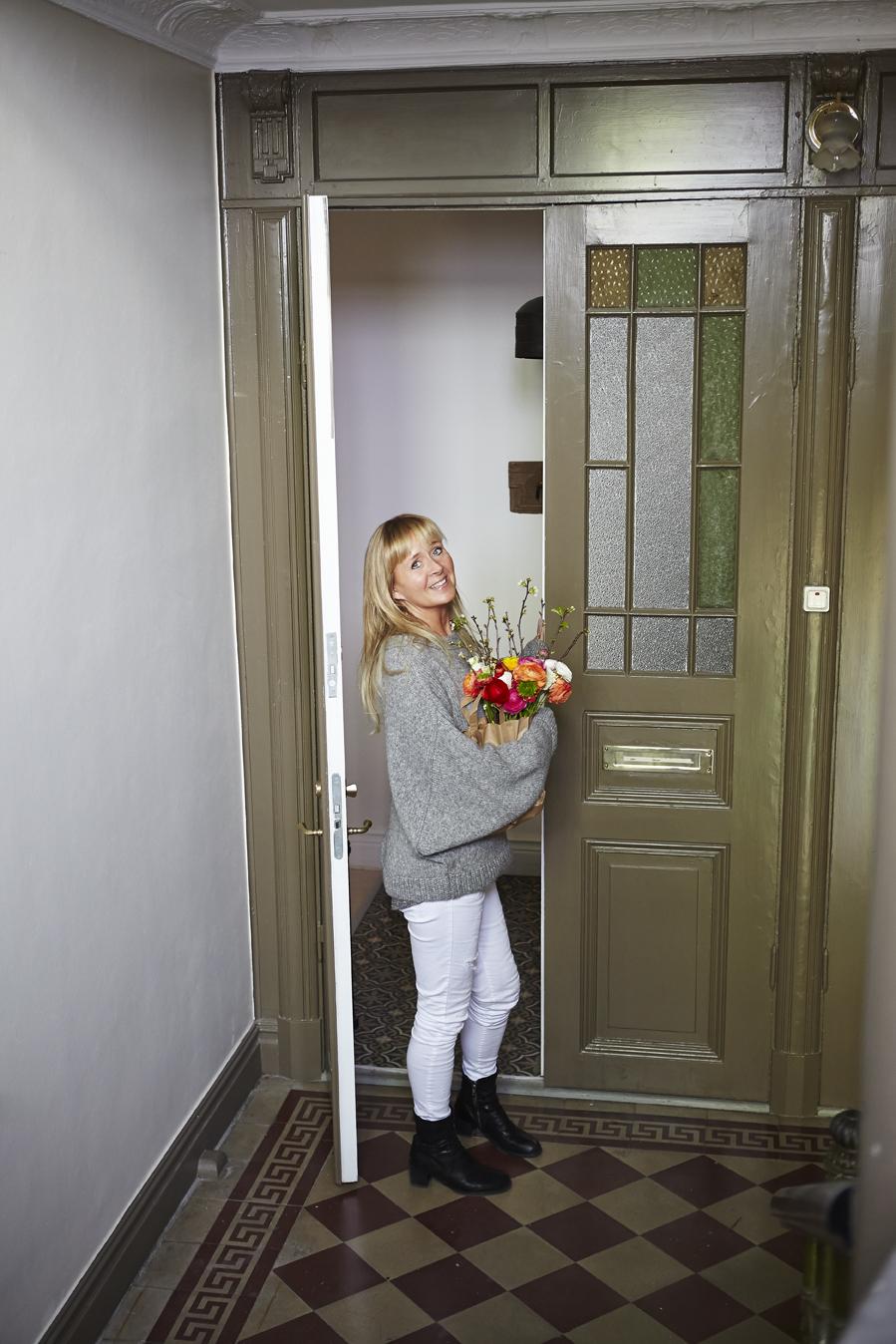 Madeleine Olsson vid de välkomnande pardörrarna med blyinfattade fönster.
