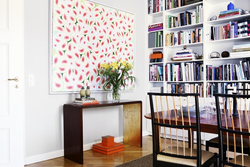 Matbord och stolar kommer från Svenskt tenn, och längs väggen löper höga bokhyllor.