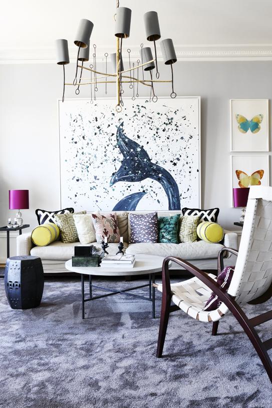 Vardagsrummet går i en behaglig gråskala med flera olika färgklickar.