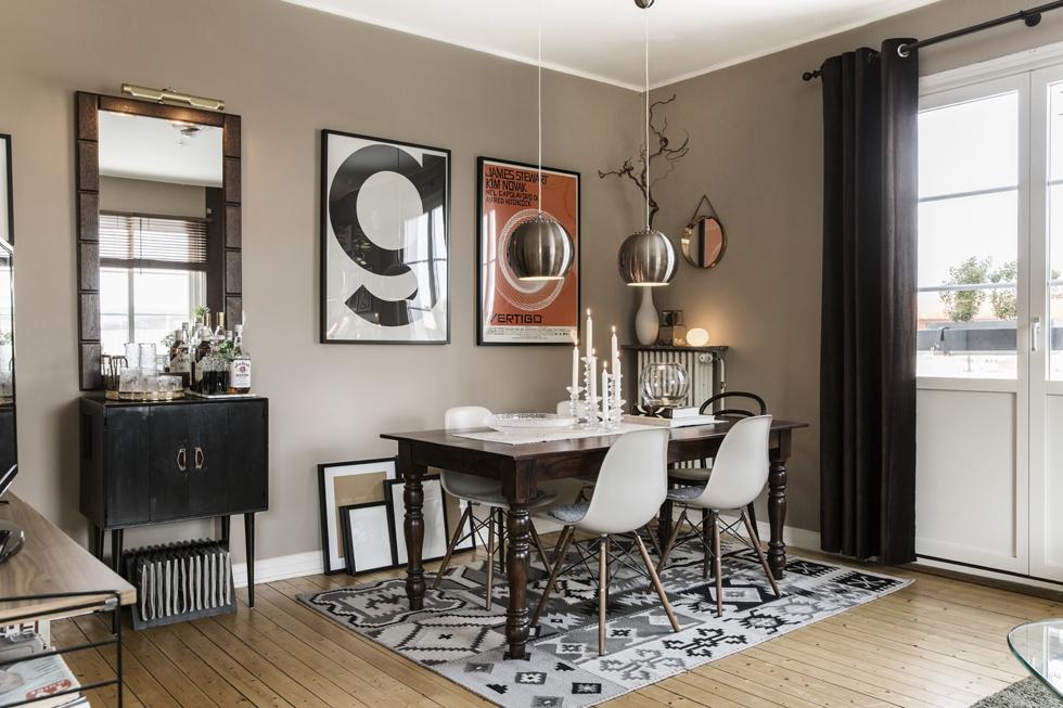 I vardagsrummet står ett rustikt matbord med klassiska Eames-stolar. På golvet ligger en matta från Rusta och i taket hänger lampor från Markslöjd. Den grafiska postern kommer från Market 29.