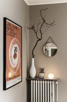Affischen i orange har motiv från Alfred Hitchcocks Vertigo, eller Studie i brott som den fick heta i Sverige, från 1958. Regissörens stil har inspirerat Andreas mycket vad gäller färg, form och känsla i inredningen. På marmorskivan ovanpå elementet står blandade loppisfynd. Den runda spegeln på väggen är en utfartsspegel från Biltema.