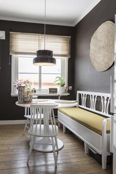 I köket bryter de vita möblerna av fint mot de mörkbruna väggarna.Ovanför köksbordet hänger en Bumlinglampa och på väggen en rund matta från Granit.