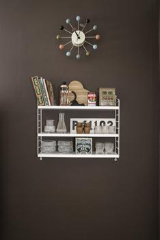 På väggen i köket sitter en pockethylla från Stringfylld av loppisfynd från bland annat Iittala. Klockan är George Nelsons Ball clock.
