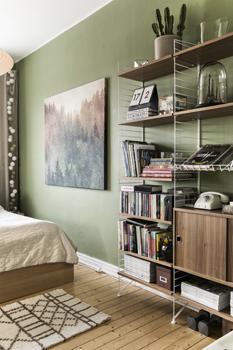 Grönt, skönt och avkopplande. Andreas ville ha grönt i sovrummet eftersom det är en lugnande färg. I hörnet hänger en ljusslinga från Happy lights. Tavlan har beställts från Society6 och mattan kommer från Åhléns. Stringhyllan är full av böcker, tidningar och dekorativa prylar.