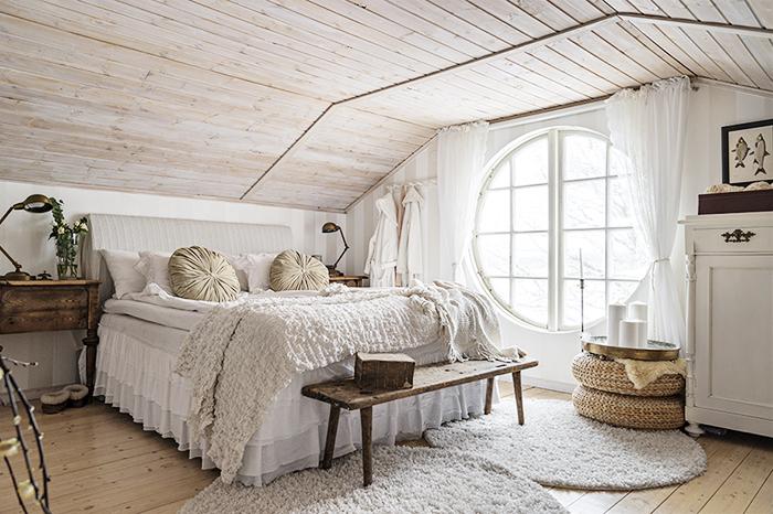 Sovrummet är inrett i olika nyanser av beige och grått. Den ljusa känslan förstärks av ljusinsläppet från det stora runda fönstret. Överkastet är köpt på Ikea och de runda kuddarna är köpta på loppis. Bänken vid fotändan är köpt på en loppis i Kristinehamn.