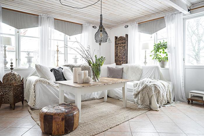 I vardagsrummet finns en soffhörna som gjord för mys. Soffbordet är ett gammalt köksbord som Sara har sågat av benen på, och sedan slipat och målat. Soffan kommer från Wermlandsmöbler och sittpuffen är köpt på loppis. Kuddarna och plädarna kommer från Ikea.
