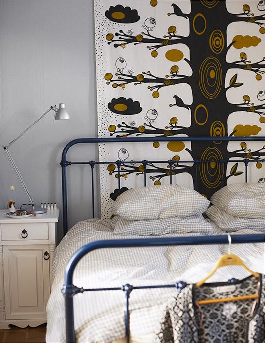 Tyget från Spira får dekorera väggen i stället för en tavla. Sängen är en bröllopsgåva. Sängborden är tillverkade av Lottas morbror. Sängkläder ochlampa från Ikea.