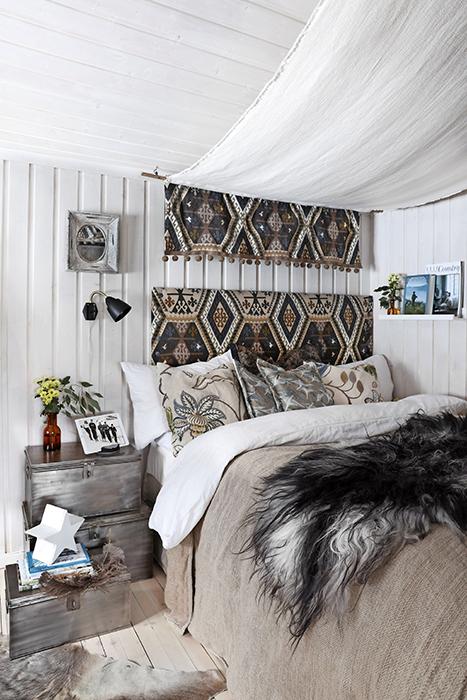 Sovrummet får en exotisk och romantisk känsla av sänghimlen, sängaveln och kuddarna gjorda av tyg från Mullberry. Plåtlådorna bredvid skapar en spännande stilkrock mot de mjuka textilierna.