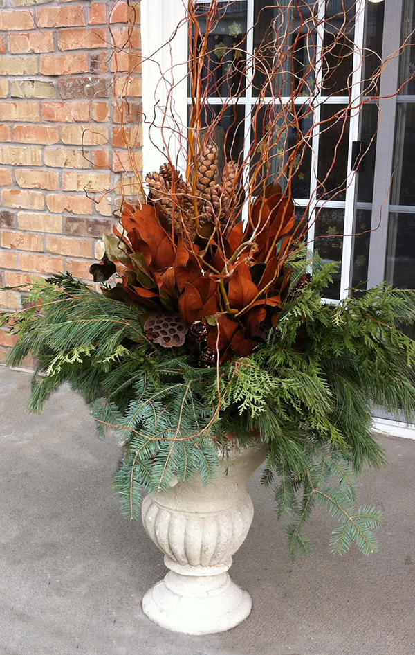Curly Willow crowns this beautiful urn with strobus cones, magnolia, lotus pods and mixed evergreens. A custom design by The Branch Ranch.
