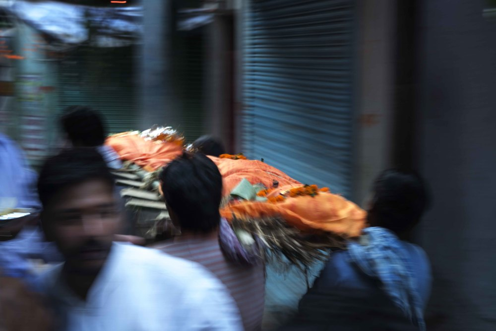The swathed bodies of the deceased are carried through the streets by the grieving family to the burning ghats