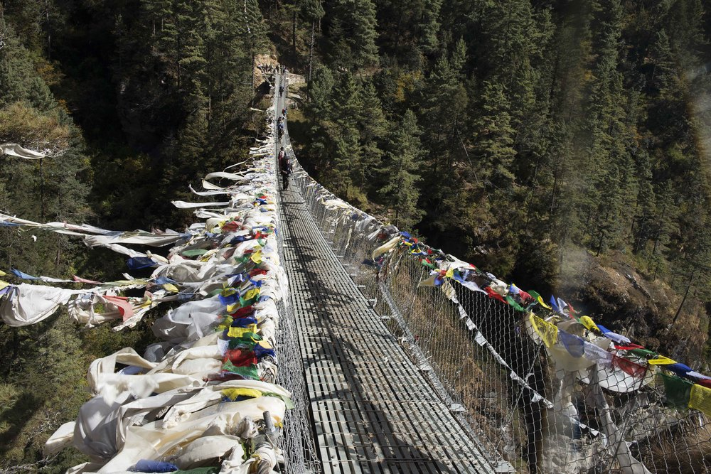 This suspension bridge had prayer flags draped over the top cables, they were blowing in the strong winds, parallel to the ground, it brought the bridge to life.