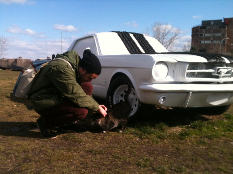 Artist Ates Ucul petting one of the park cats by Hugh Hayden's the art car piece