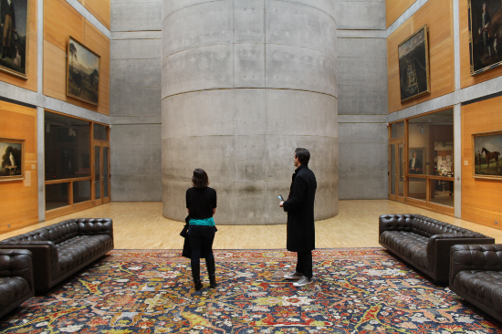 Chesterfield sofas sit on a patterned rug offset by the concrete and wood framing the collection of paintings.