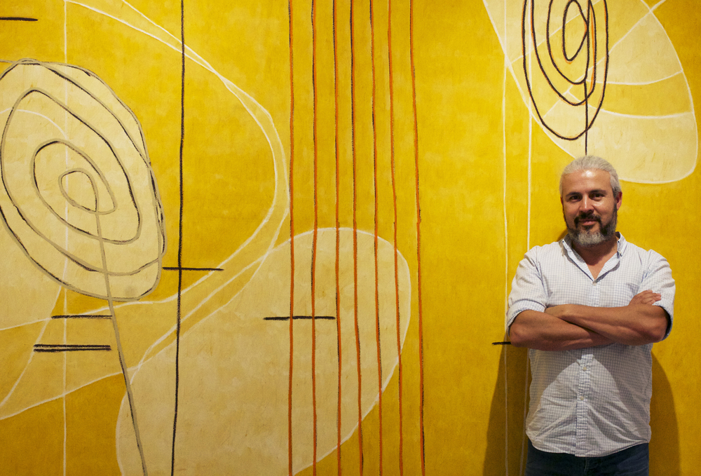 Colombian painter Mario Velez stands in front of one of his monumental pieces.