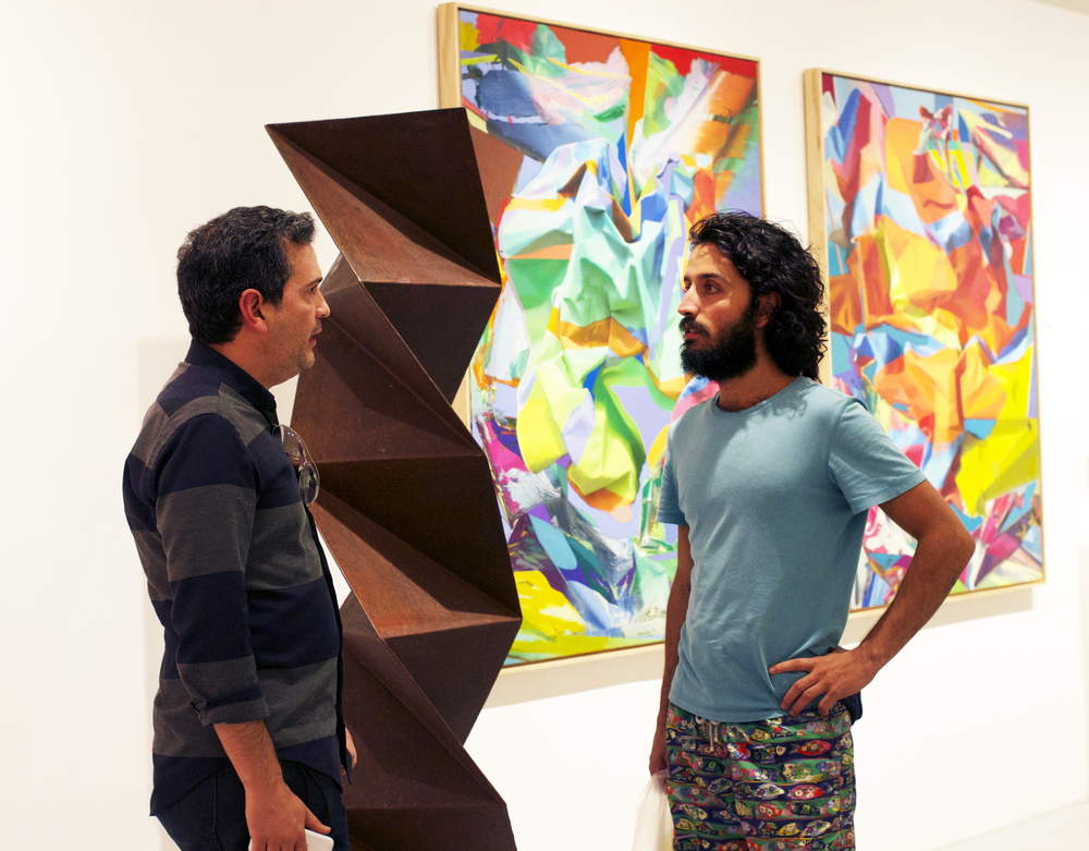 "Colombian sculptor Juan Mejia discusses his piece, ""Origami,"" with a friend."