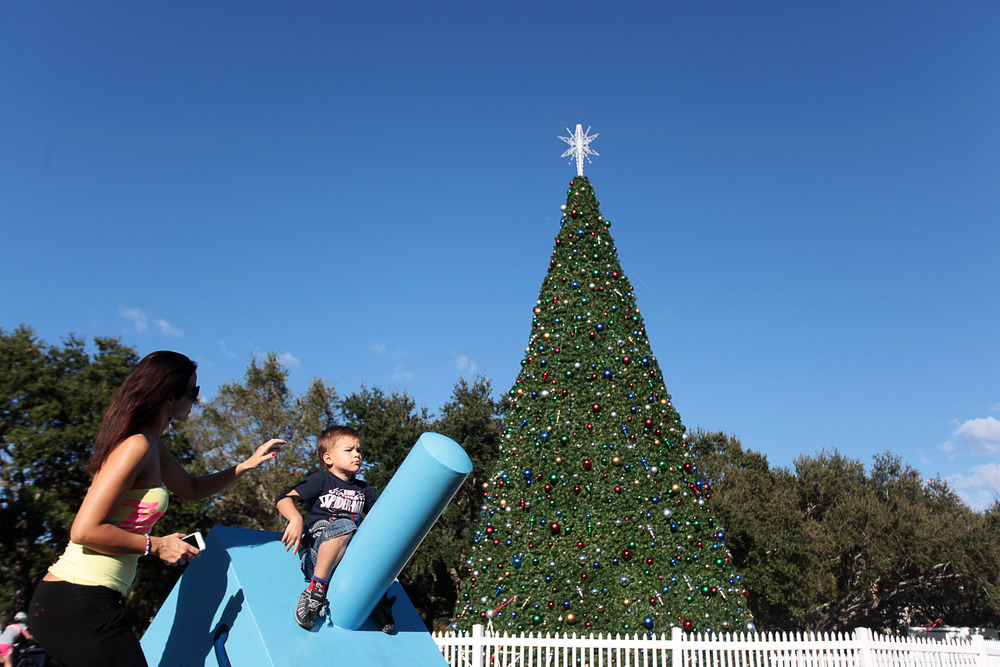 Heidi Grimes, of Hungary, adjusts her son, Hunor Miwok's, hair as he sits on a giant dreidel in the St. Petersburg Christmas display on Sunday November 30th, 2014.