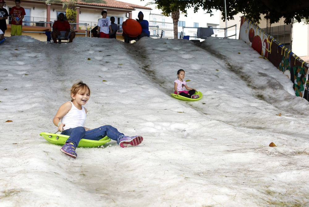 Alexandra Deleyska, 7, sleds down a giant snow hill during Snowfest at North Straub Park on Saturday December 6th, 2014. St. Petersburg Parks and Recreation brought 65 tons of snow in for the event that followed the 88th annual Santa Parade on Saturday morning.