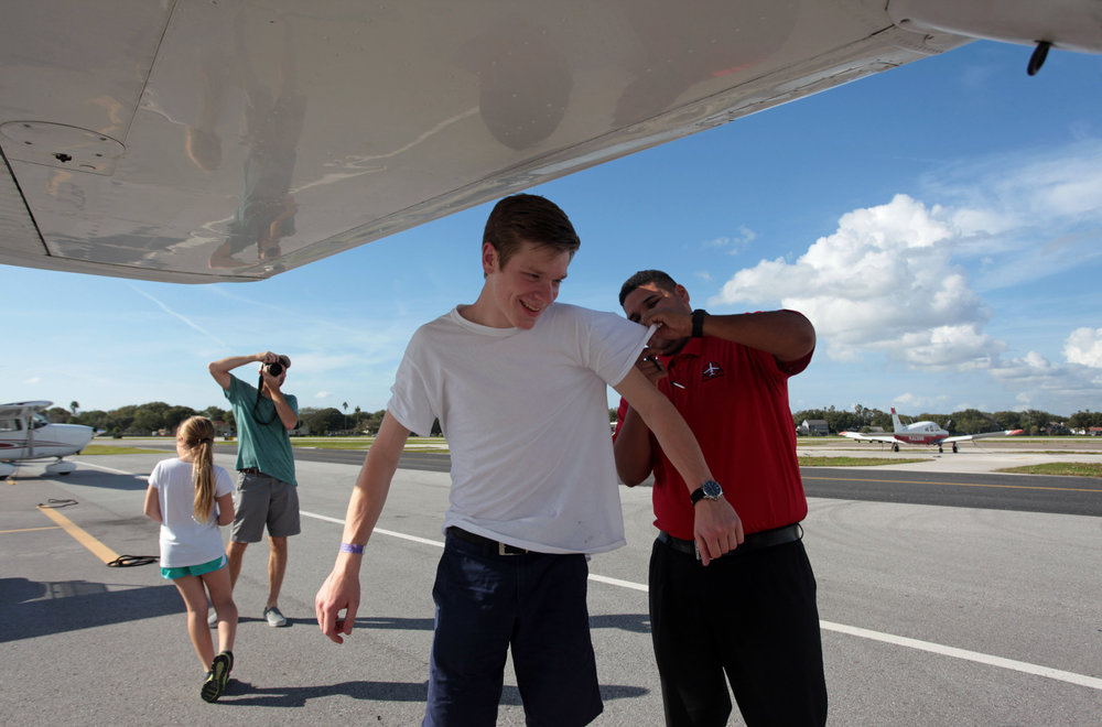 (left to right) Addy McDowell, 8, and Todd McDowell watch as Wyatt McDowell, 16, has his shirt cut by flight instructor Miguel A. Perez Albarran, 24, after Wyatt took his first solo flight in a Cessna 172 on Saturday January 3rd, 2015 from Peter O. Knight Airport at Davis Islands in Tampa.