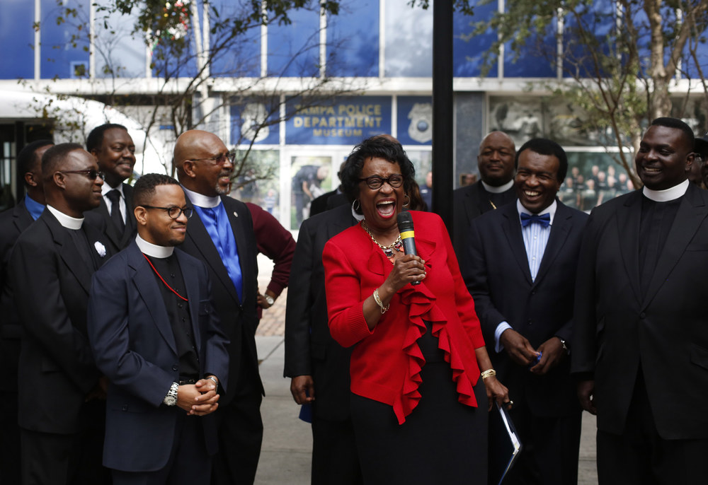 Florida Senator Arthenia Joyner laughs with clergy members while speaking at Gaslight park, in front of the Tampa PD, at the march for peace on Thursday January 1st, 2014.