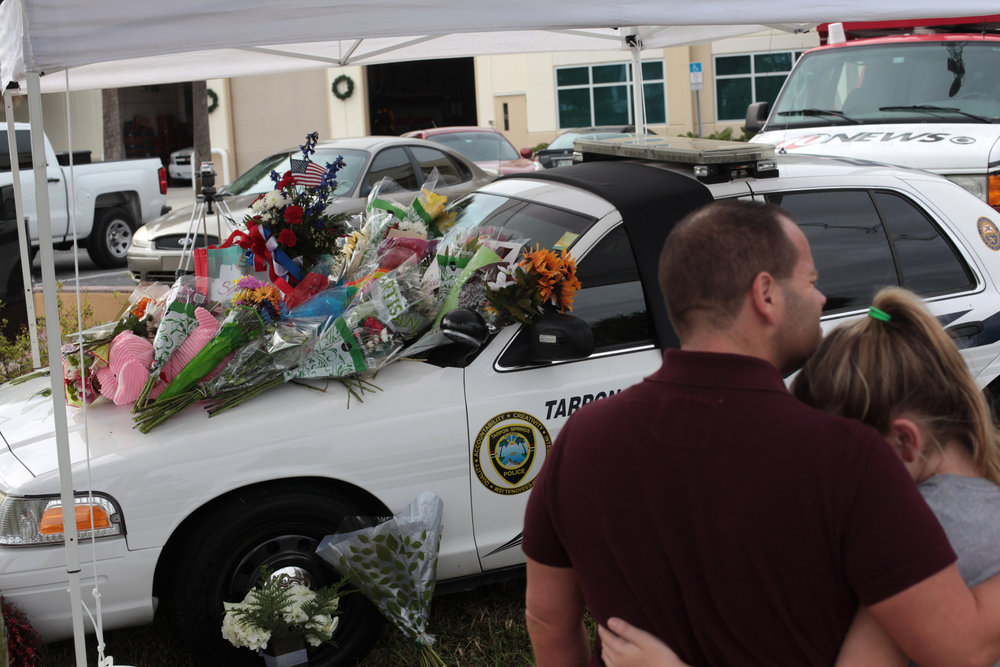 Keith Baldwin embraced Kimberly Baldwin, 11, of Tarpon Springs, beside the memorial for Tarpon Springs police officer, Charlie Kondek, 45, outside of the public safety facility in Tarpon Springs on Sunday December 21st, 2014.