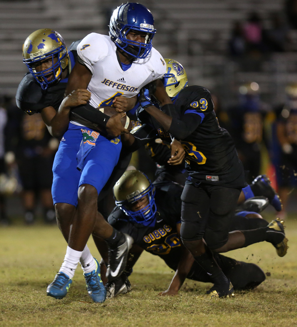Jermaine Eskridge (4) of Jefferson, tries to escape Gibbs defenders during the fourth quarter of the  regional quarterfinal on Friday November 12, 2015 at Gibbs High School in St. Petersburg. Jefferson defeated Gibbs, 45 to 44.