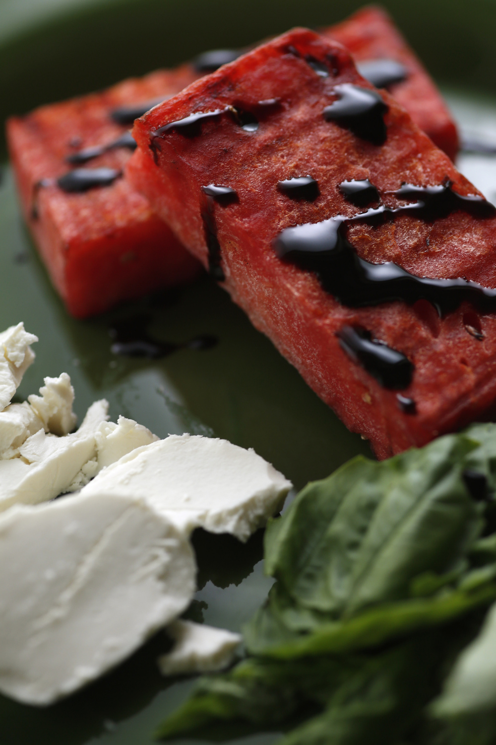 Grilled watermelon, served with mozzarella and basil, and topped with a balsamic glaze
