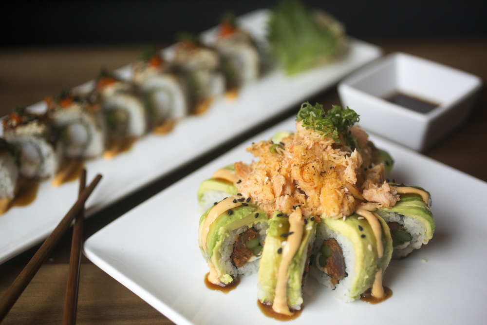 The Category 5 roll at Souzou, has spicy tuna, cream cheese, asparagus, and is topped with avocado, kabayaki sauce, chili aioli, dynamite mix, and scallion.