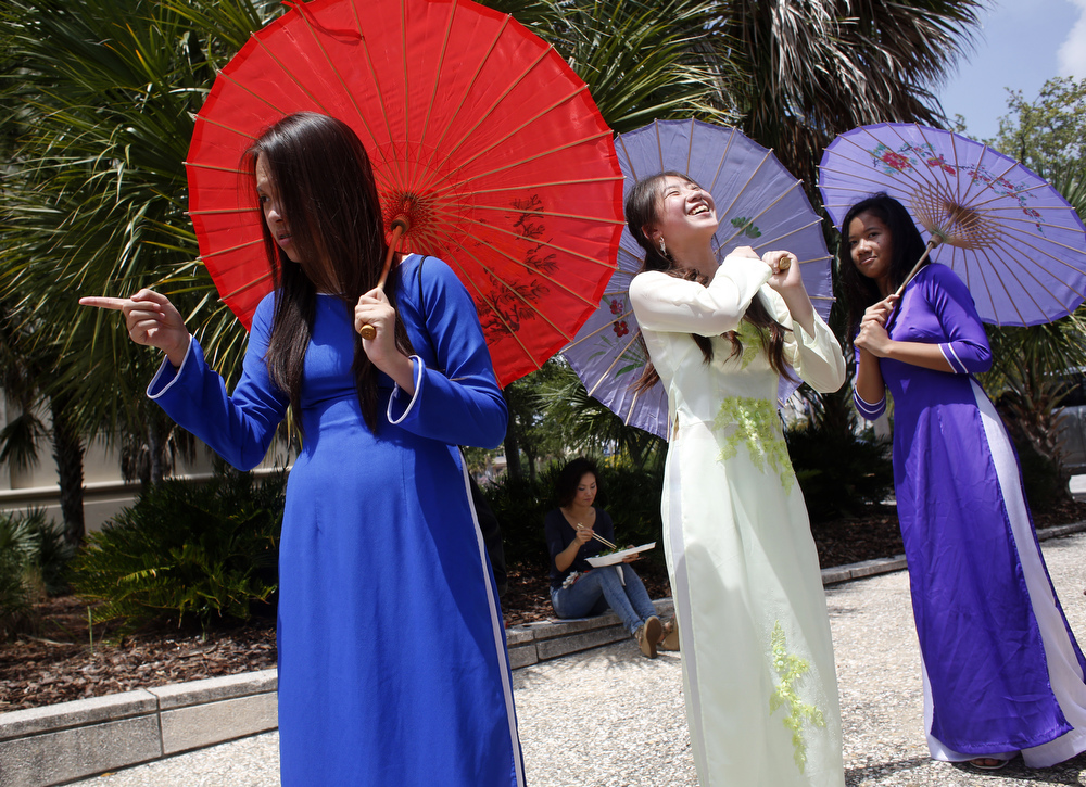 (left to right) Milli Nguyen,14, Jenny Tran, 14, and Binh Thach, 13, practice with their Vietnamese dance group from the Lealman and Asian Neighborhood Family Center before performing the umbrella dance at Asia Fest on Saturday April 25th, 2015 at Cotanchobee Park in Tampa.
