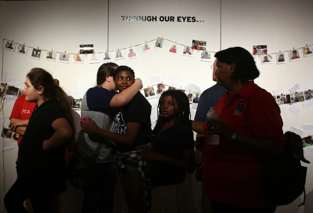 Gracie Gordy, 13, hugs Kaylee Pompey, 13, both John Hopkins students, at the opening night of Through Our Eyes: Midtown and Beyond on Friday November 6, 2015 at Studio 620 in downtown St. Petersburg. The exhibit features photographs and multimedia work of students from Melrose Elementary, John Hopkins Middle, and Lakewood High School.