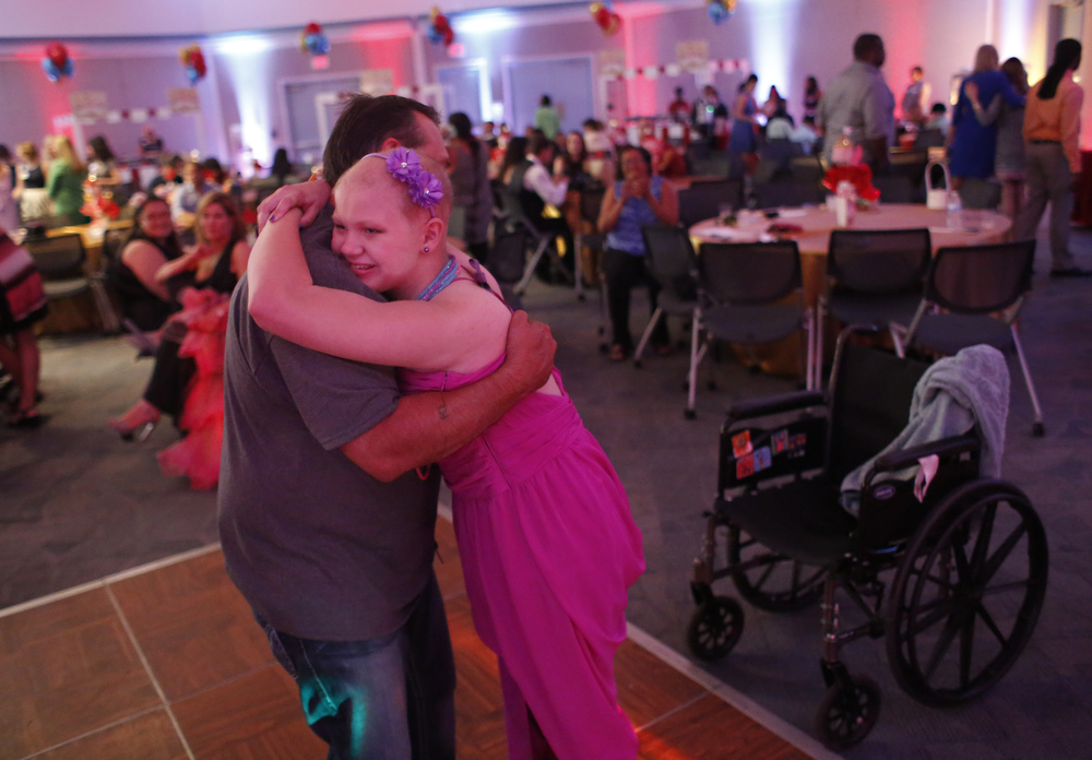 "(right) Jo Spivey, 13, dances with her stepdad Russell Lee, of Brandon, during the fifth annual prom on Friday May 1st, 2015 at St. Joseph's Children's Hospital in Tampa.   Current and former pediatric patients enjoyed a Big Top Circus-themed prom complete with music, dancing, refreshments, and keepsake photos. ""Just to be able to have her up and out of the wheelchair, it felt so good,"" Lee said. ""I hope that next year I'll be up here dancing with her."""