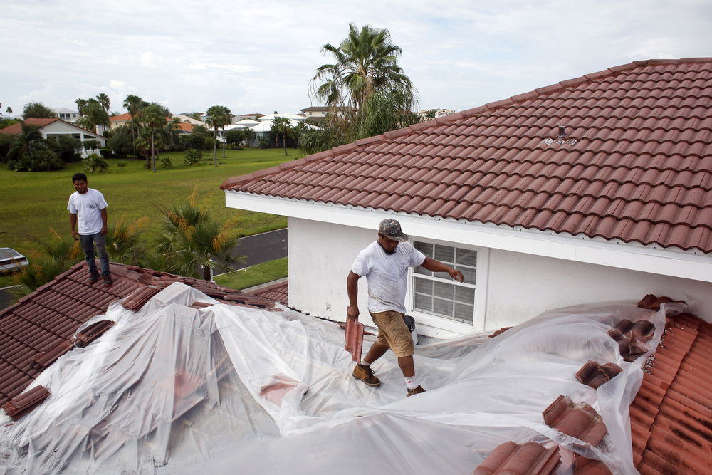 (left to right) Jose Palacios and Wilmer Puerto, of Cardinal Roofing, cover the roof of a home in plastic to protect it from the rain on Friday July 31, 2015 in Apollo Beach. Every rainy season work gets delayed for Cardinal Roofing because of frequent rain showers. According to Roger Jenkins, one of three owners, a 10 to 12 hour day could mean only four hours of work between waiting out the rain in the truck.