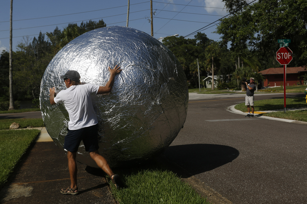 Piotr Janowski took the tin foil that was wrapping his home and covered a giant beach ball with it, to roll to the nearby recycling bins on Thursday July 9th, 2015, in Tarpon Springs. Janowski, who is an artist from Vienna, covered his home in May, in his first outdoor art installation. Though this project was self funded, Reynolds Wrap is providing sponsorship for his future works.