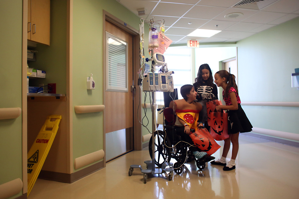 "Triplets Diana, Elizabeth and Amanda Orama, all 11 and of Sarasota, wait in the hallway of All Children's Hospital during trick or treating on Friday October 30, 2015 in downtown St. Petersburg. ""Pretend today is Halloween, just for me,"" Diana Orama said to her sister Amanda Orama."