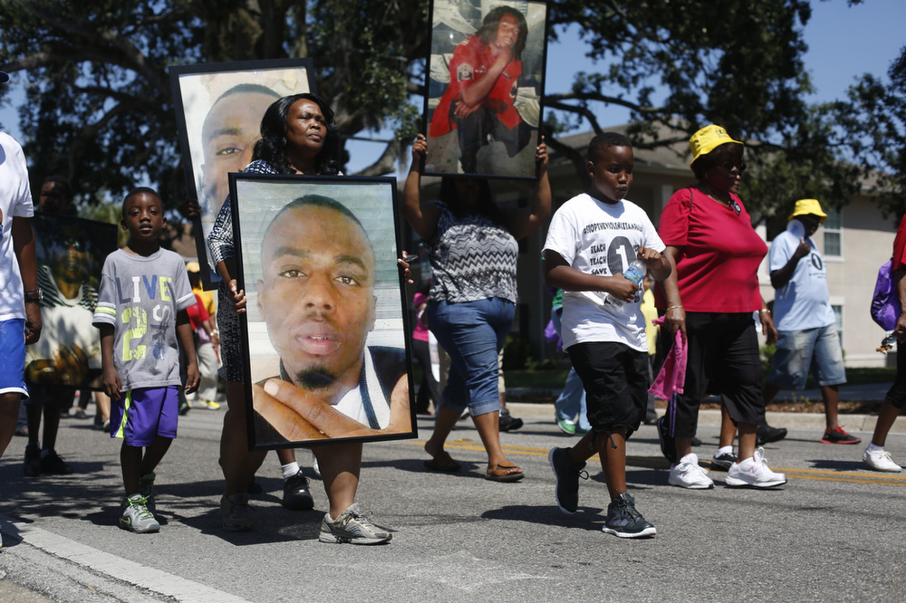 Tonya Mosley (second from left), of Tampa, marched down Lake Avenue carrying a photograph of her son Aviance Mosley, during a unity march on Saturday May 9th, 2015, in Tampa. Tonya Mosley's son was killed in Tampa on March 29, 2014.