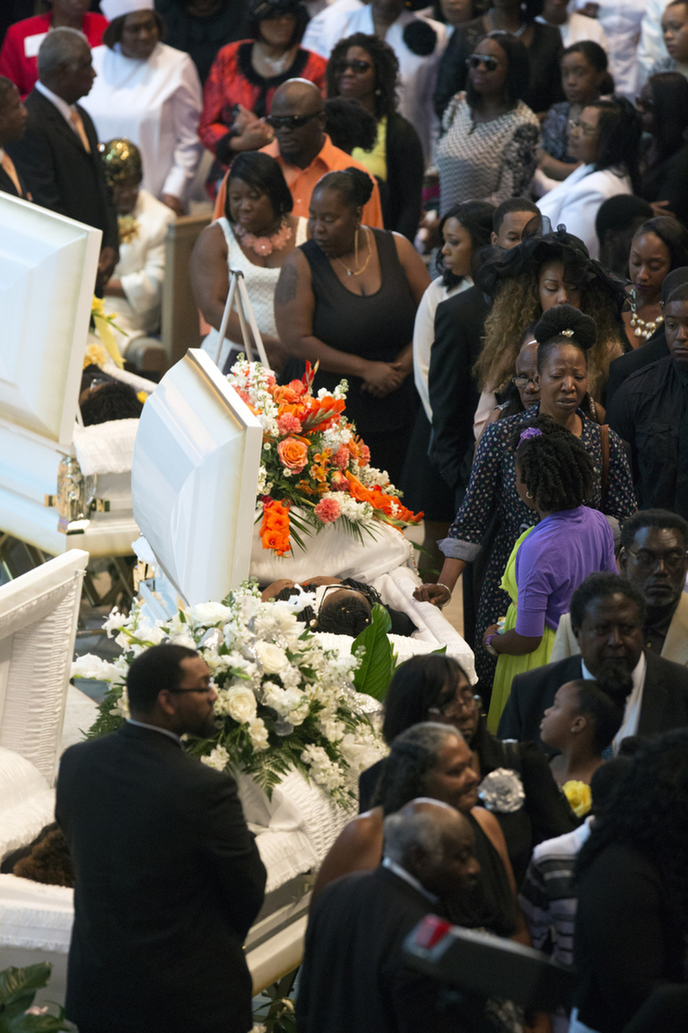 Mourners view the caskets at the funeral of sisters LaMour, 29, India, 24, and Tehira Welch, 18, at First Baptist of St. Petersburg on Saturday August 15, 2015. The three Welch sisters died in a car accident last Sunday, on the way home from a religious convention in Fort Pierce.
