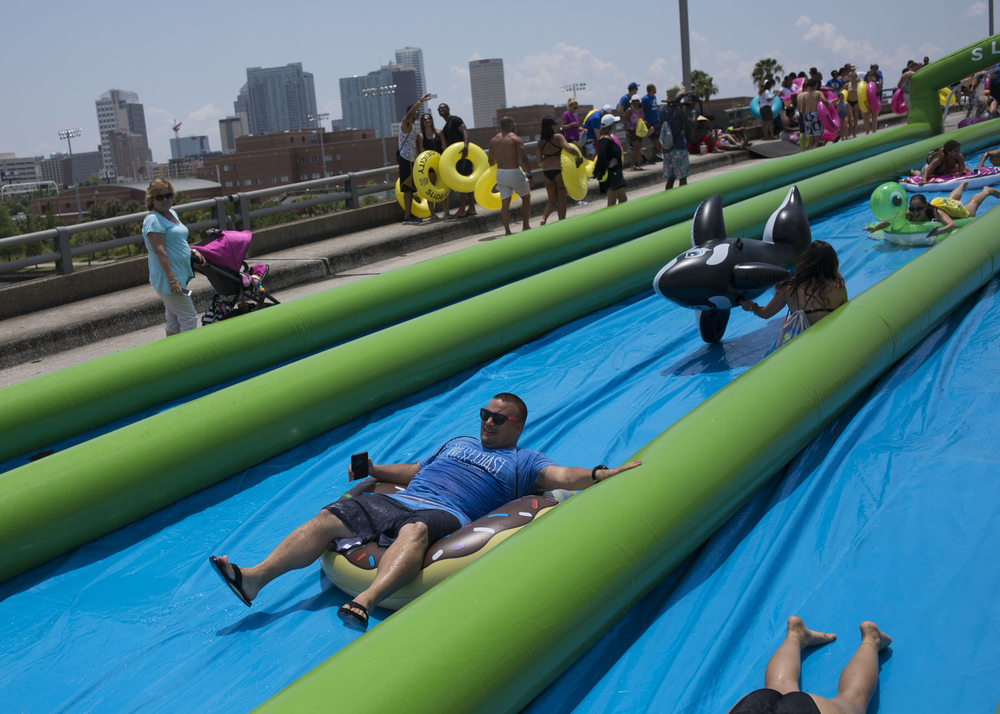 (center) Bryan Parlee, of Tampa, slides on a donut-shaped tube at Slide the City, a one thousand foot water slide across the North Boulevard Bridge on Saturday May 14, 2016 in Tampa.