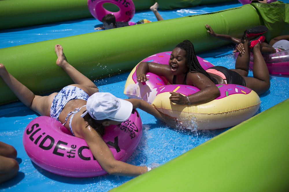 (Center) Rhonae Tucker of Tampa, slides on a donut shaped tube at Slide the City, a one thousand foot water slide across the North Boulevard Bridge on Saturday May 14, 2016 in Tampa.