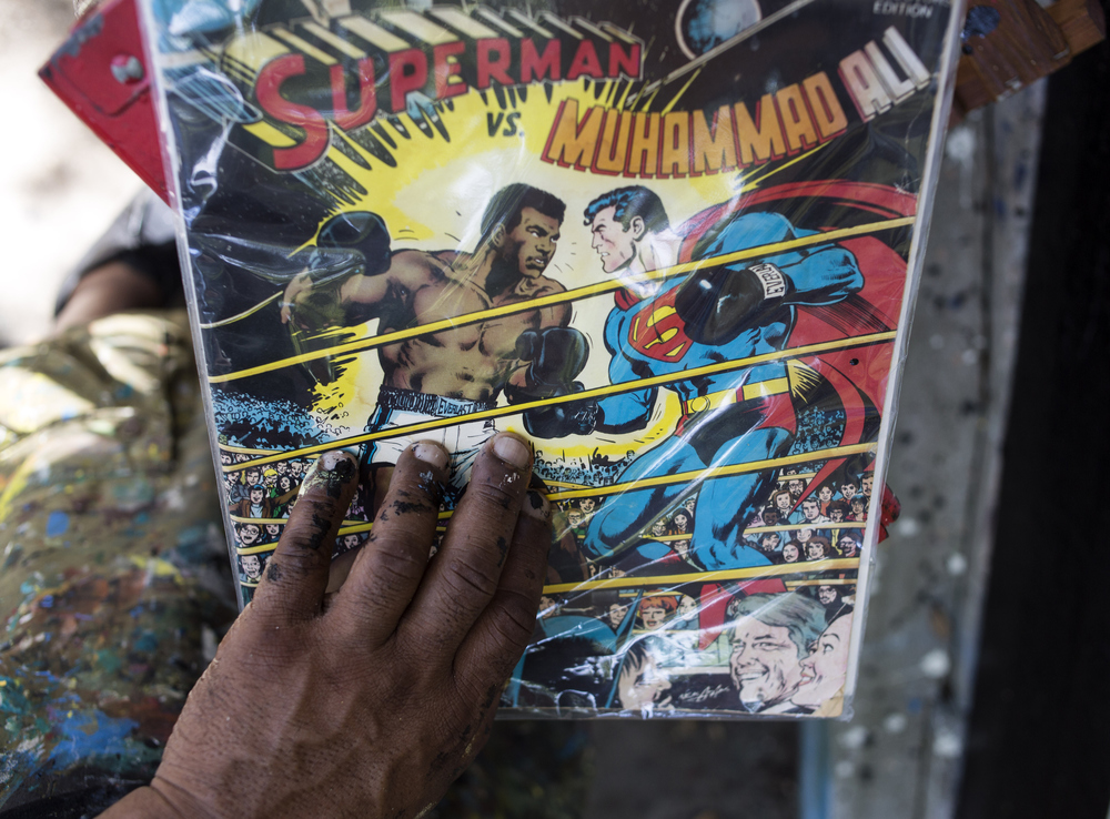 "Rasta Geary Taylor, of St. Petersburg, paints a mural of Muhammad Ali inspired by this comic book on Saturday June 4, 2016, behind his gallery/studio space, 1 of 1 Customs.  ""I thought I'd pay my respects, and do this piece for the city,"" Taylor said."
