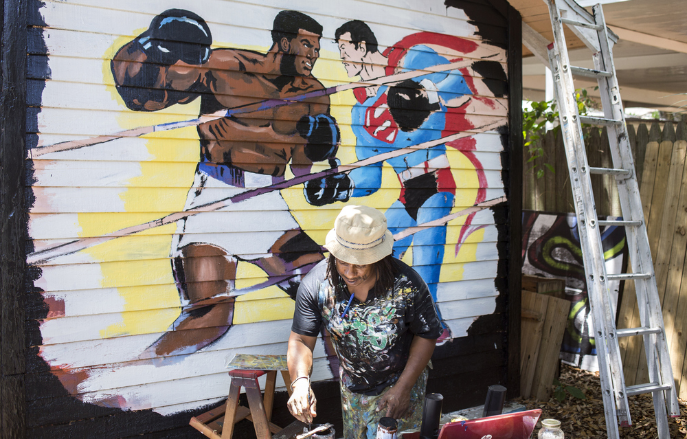After inspiration struck him in his sleep, he started painting around 5:30 Saturday morning, and hoped to finish by sundown.   The painting is based on a 1975 DC Comic Book, Superman vs. Muhammad Ali. While working, Taylor listened to Muhammad Ali fights and interviews.