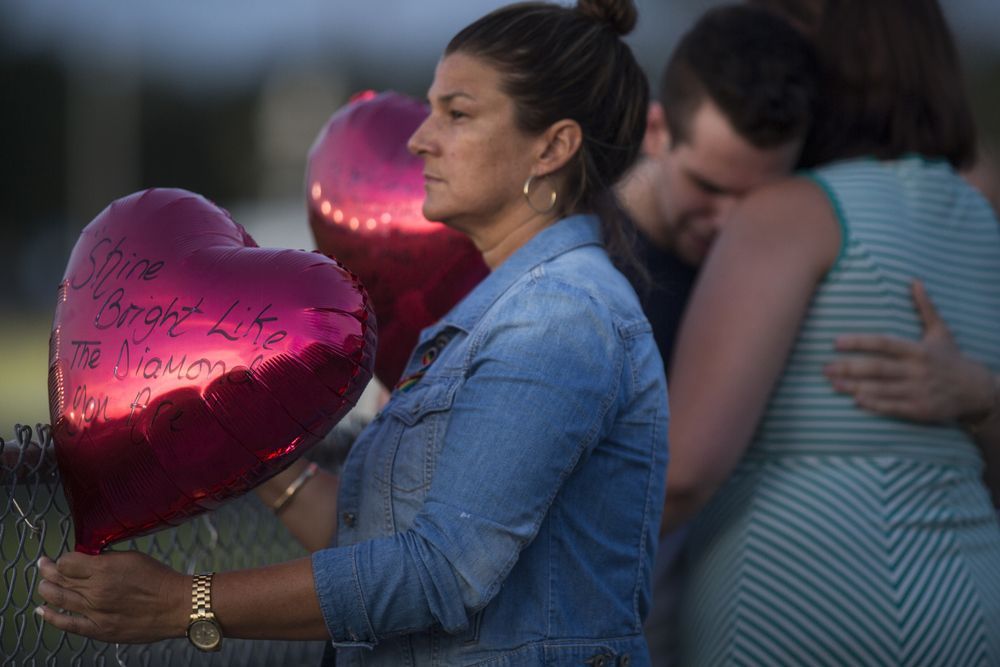Family and friends gathered for a vigil in memory of Christopher Sanfeliz, 24, at Gaither High School in Tampa on Wednesday June 15, 2016.  Christopher's aunt Marlene Alonso holds a ballon during the ceremony.
