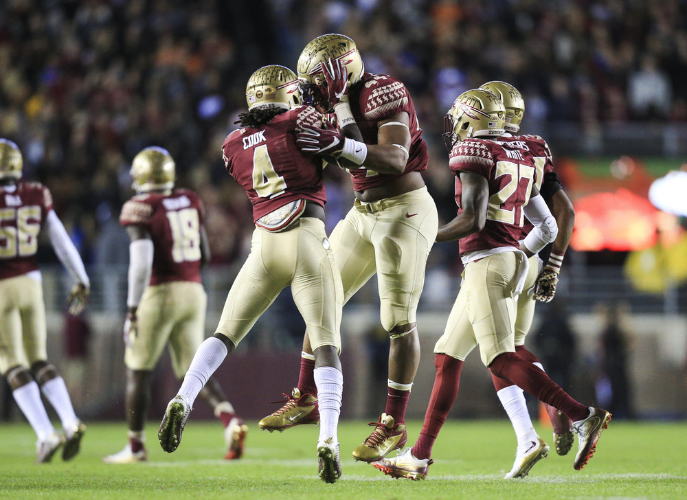 Florida State Seminoles running back Dalvin Cook (4) with Florida State Seminoles defensive end DeMarcus Walker (44) after the fumble recovery in the first quarter of the game between the Florida State Seminoles and the Florida Gators at Doak Campbell Stadium in Tallahassee, Fla. on Saturday, Nov. 26, 2016.