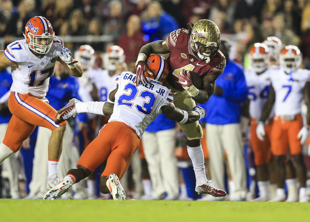 Florida State Seminoles running back Dalvin Cook (4) brought down by Florida Gators defensive back Chauncey Gardner (23) on a run in the first quarter of the game between the Florida State Seminoles and the Florida Gators at Doak Campbell Stadium in Tallahassee, Fla. on Saturday, Nov. 26, 2016.