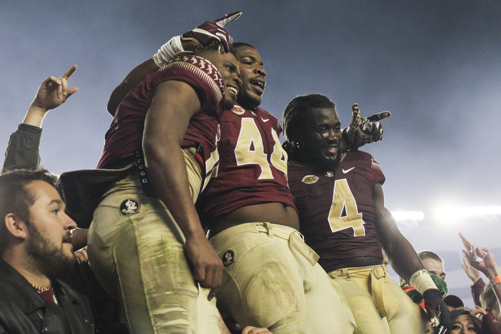 Florida State Seminoles quarterback Deondre Francois (12), defensive end DeMarcus Walker (44) and running back Dalvin Cook (4) celebrate in the stands after the game between the Florida State Seminoles and the Florida Gators at Doak Campbell Stadium in Tallahassee, Fla. on Saturday, Nov. 26, 2016.  Final score was Florida State 31, Florida 13.