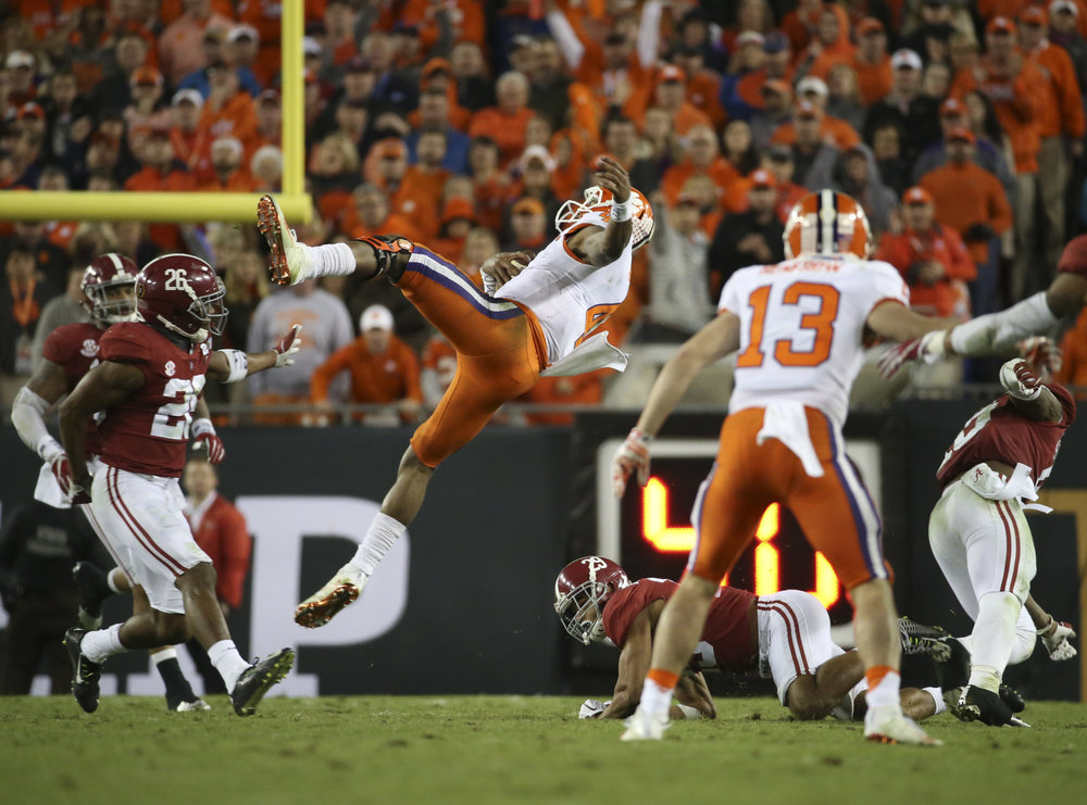 Clemson Tigers quarterback Deshaun Watson (4) gets spun after being hit on a run during the third quarter at the College Football Playoff National Championship on Monday January 9, 2017 at Raymond James Stadium, in Tampa, Fla.